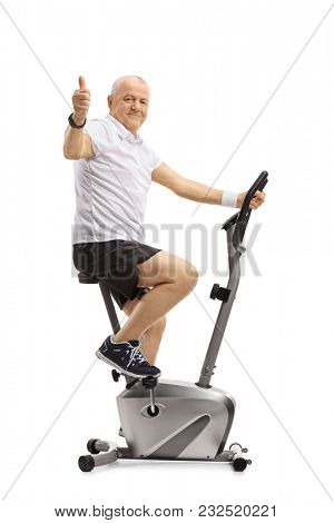 Mature man exercising on a stationary bike and making a thumb up gesture isolated on white background