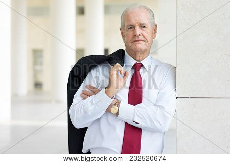Closeup Portrait Of Serious Senior Man In Formalwear Holding Jacket Over Shoulder. Experienced Finan