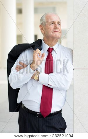 Portrait Of Pensive Senior Man In White Shirt And Tie Holding Jacket Over Shoulder. Executive Thinki