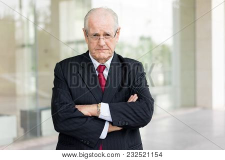 Portrait Of Unhappy Senior Man In Suit With Arms Folded. Tired Executive Thinking Over Business Trou