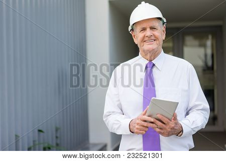 Smiling Senior Man In Tie And Helmet Using Tablet At Construction Site. Chief Engineer Reviewing Sit