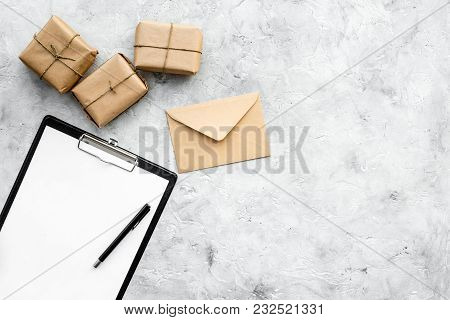 Courier Workplace With Cardboard Box And Envelopes For Delivery On Stone Desk Background Top View Mo