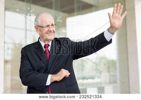 Smiling Senior Man In Suit Waving With Hand To Partner Outdoors. Boss Greeting Employees Near To Off