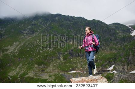 Smiling Female Climber With Walking Sticks Looking To Side While Reaching Rock Top With Beautiful Gr
