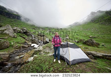 Woman Tourist With A Backpack And Trekking Sticks Near The Tent In The Valley Of The Romanian Mounta
