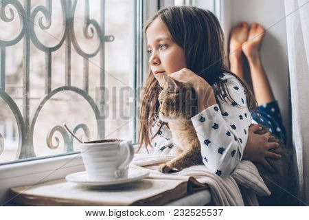 Child in pajamas relaxing on a window sill with pet. Lazy weekend with cat at home. Cozy scene, hygge concept. poster