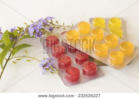 Cough Sore Throat Pastille With Purple Flowers On Background White