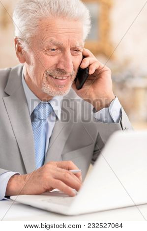Smiling  Elderly Man With Phone In Office