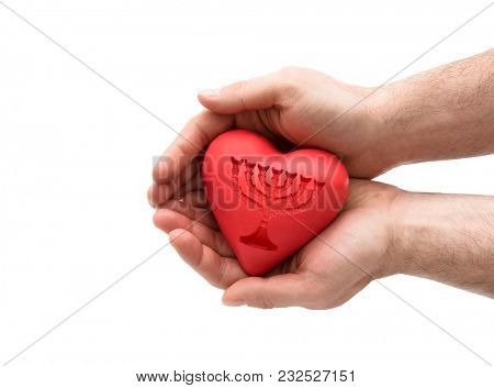 Red heart with imprinted menorah in man's hands.