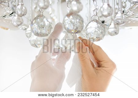 Closeup Of Hands Cleaning The Chandelier With Rag