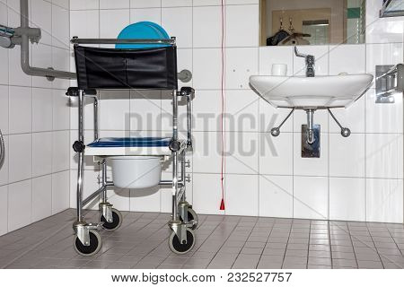 Wheelchair With Included Toilet Pan In Retirement Home.