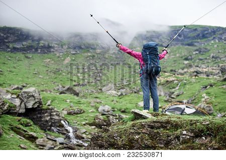Rear View Low Angle Shot Of A Female Hiker With A Backpack Spreading Her Arms With Trekking Poles In