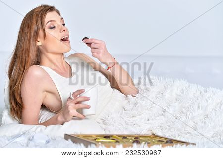 Young Woman In Bed Relaxing At Home With Cup Of Tea