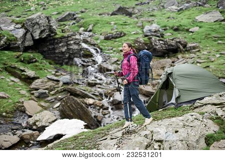Cheerful Young Woman Hiker Smiling Walking In The Mountains Valley With Trekking Poles Tent On The B