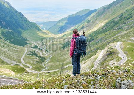 Young Female Tourist From The Back Looking To Breathtaking View Of Winding Transfagarshan Road Among