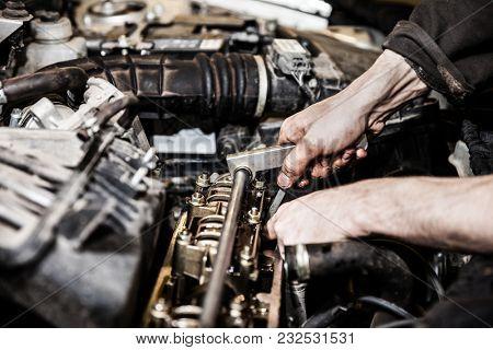 Automobile service worker or garage mechanic hand holding vehicle motor maintenance tool repairing auto car engine