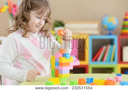 Cute Little Girl Playing With Colorful Plastic Blocks In Room