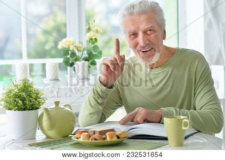 Senior Man  Reading Book While Drinking Tea At Home