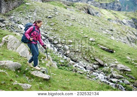 Young Female Climber Hiking In The Mountains With Her Backpack And Trekking Poles Copyspace Explorin