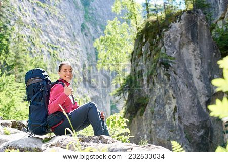 Cheerful Young Woman Smiling Joyfully Showing Thumbs Up Sitting On Top Of A Rock Resting With Her Ba