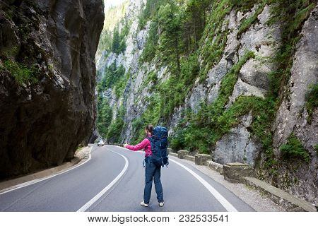 Tourist Female With Backpack Is Catching A Car On Road In The Bicaz Gorge. Bicaz Canyon Is One Of Th