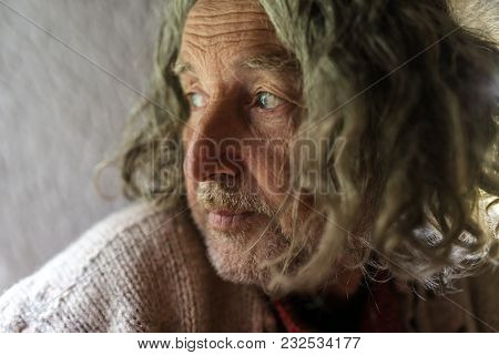 Portrait Of Old Man Wit Long Gray Hair And Stubble Looking Sad, Side View.