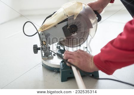 Builder Using A Small Electric Circular Saw To Cut A Length Of Plastic Profile