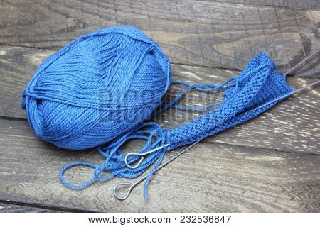 Tangle Of Thread And Knitting Needles Against The Background Of Boards