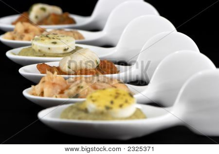 ceramic spoons with starter food on a