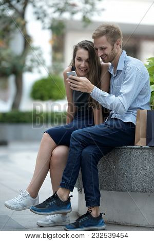 Cheerful Couple Using Smartphone Application Together After Shopping