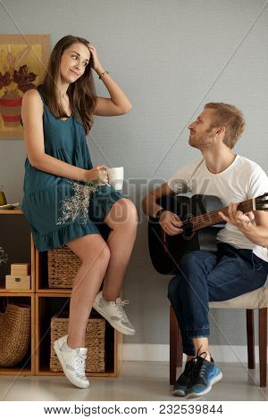 Young Woman Listening To Her Boyfriend Playing Acoustic Guitar At Home