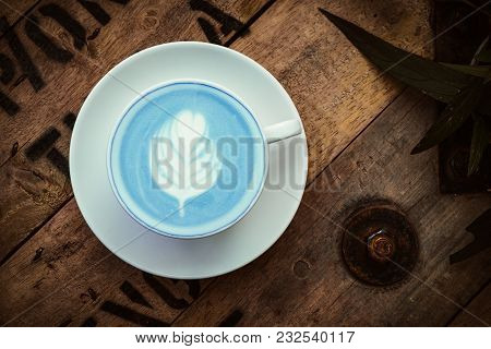 A White Cup Of Hot Milk Butterfly Pea Latte Art On The Wooden Table In Coffee Shop. Top View With Re