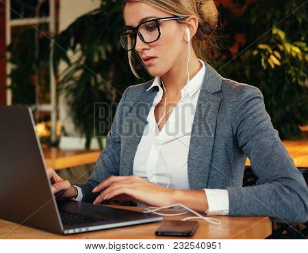 Businesswoman Working On Laptop In Coffee Shop. Young business woman uses laptop in cafe. Lifestyle and business concept.