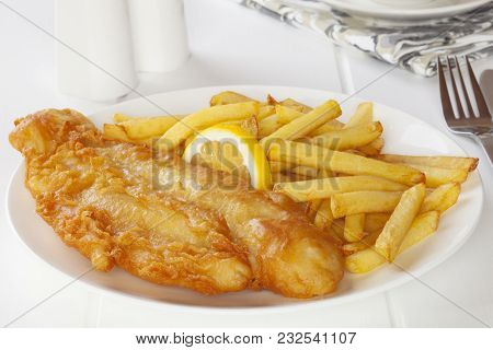 Battered Fish With Chips In A Light, Bright Setting.