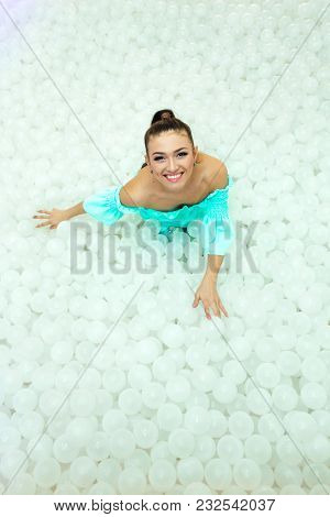 Happy Beautiful Woman Lays Surrounded By White Plastic Balls In The Dry Pool For Adult.