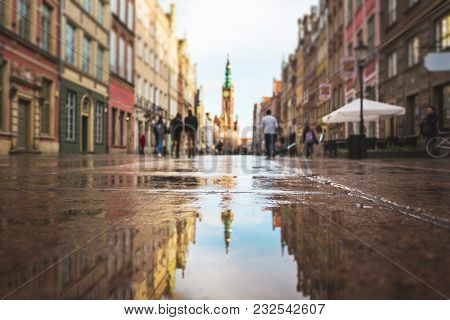 Tower Of City Hall Is Reflected In The Puddle, Focus On Puddle