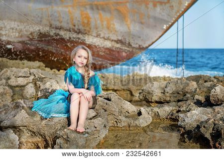 Cute Doll Girl Sitting On The Rocky Shore Of The Sea Ocean In Azure Celestial Dress Near An Abandone