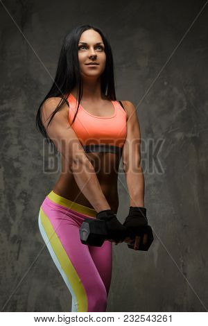 Athletic Woman In Colorful Sportswear Holds One Dumbbell.