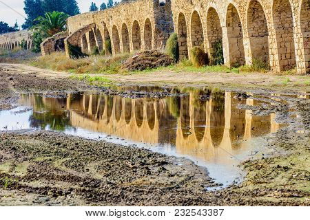 View To Old Historic Ottoman Aqueduct To Acre (acco), Israel And Puddle.