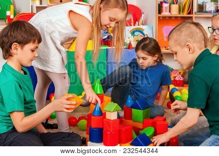 Children building blocks in kindergarten. Group kids playing toy on floor. Top view of interior preschool. Children develop their fingers in a game of cubes. Hobby for teenagers.