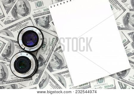 Two Photographic Lenses And White Notebook Lie On The Background Of A Lot Of Dollar Bills. Space For