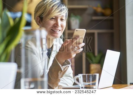 Young Asian Woman Smiling Using Smart Phone And Laptop At Coffee Shop