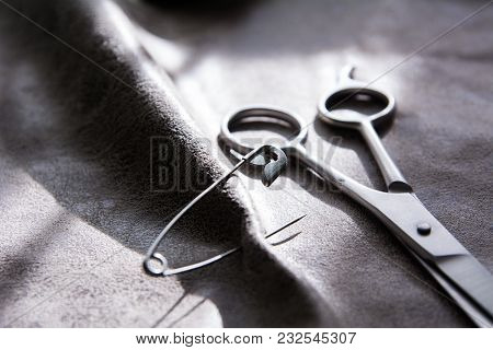 Scissors And A Pin On A Gray Fabric With A Rough Surface