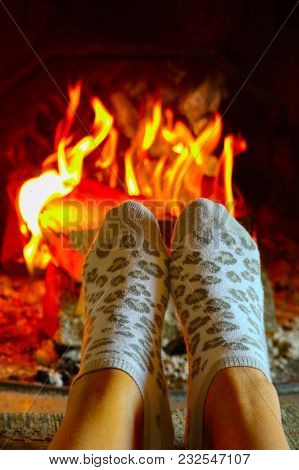 Burning Wood At The Fireplace, Female Legs In Socks Warming Up. Firewood Bricks At The Fire, Woman F