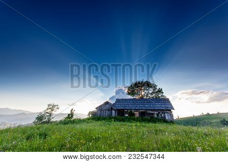 Fantastic evening sun beams in the countryside and the old hut. Location rural place of Ukraine, Europe. Scenic image of beautiful nature landscape, picturesque mountain view. Beauty of earth.
