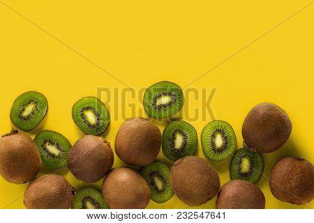 Fresh Fruits On The Yellow Background, Cut Kiwi Fruit And Kiwi Fruit