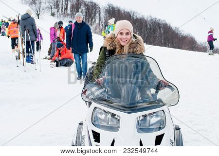 Ukraine, Lviv - 20 Mar, 2018: Beautiful Smiling Girl Sits On A Snowmobile On The Background Of Peopl