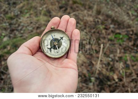 Traveler Holding Compass In Hand. Compass In A Hand Blurred Background