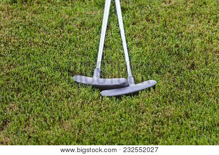 Two Putters In Grass On A Golf Course