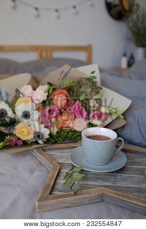 A Bouquet Of Beautiful Flowers And A Cup Of Tea On The Bed